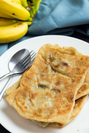 Banana paratha or pancake served in white plate with bananas Standard-Bild