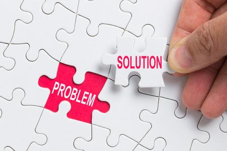 Hand, die ein Stück weißes Puzzle mit Wortproblem und Lösung hält.
