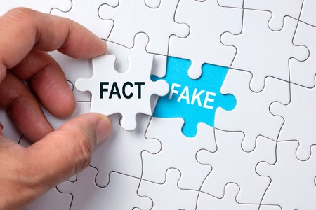 Fake word on missing puzzle with a hand hold a piece of fact word puzzle