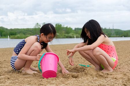 Two little Asian girls playing sand at beach with bucket and spade