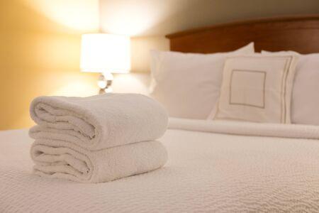 Weißes Handtuch auf dem Bett im Gästezimmer für Hotelkunden.