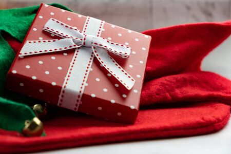 Red christmas box tied In white ribbon on a red cloth with jingle bells