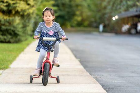 Linda niña asiática aprendiendo a andar en bicicleta sin usar un casco