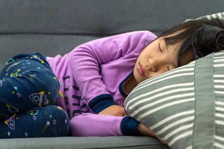 Little Asian child girl sleeping on couch with purple color pajamas Banco de Imagens - 133191194