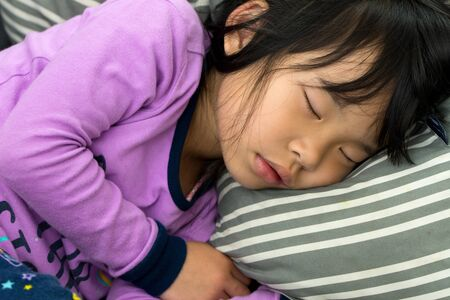 Little Asian child girl sleeping on couch with purple color pajamas