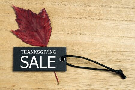 Black Friday sale label tag with autumn leaves on wooden background