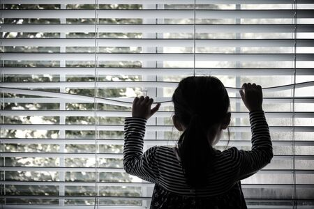 Lonely toddler child standing in front of a window looking outside