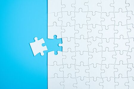 Blue background made from white jigsaw puzzle pieces and place for your content