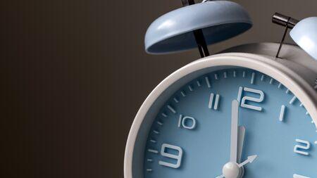 Blue color old fashioned bell alarm clock at twelve oclock, macro shot