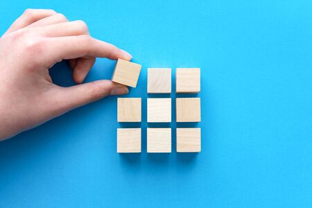 Hand arranging wood blocks in square shape for business strategy, team building or development concept