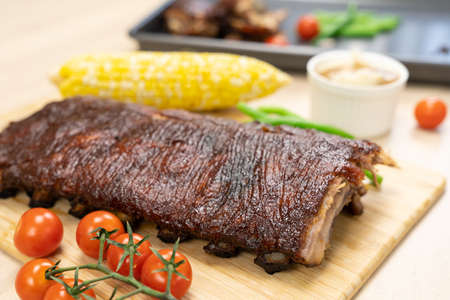 Oven baked BBQ pork ribs with sweet corn, bean and tomato Banque d'images