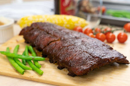 Oven baked BBQ pork ribs with sweet corn, bean and tomato Archivio Fotografico