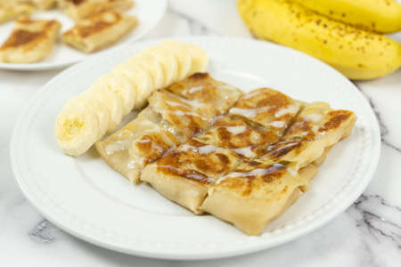 Banana paratha or pancake served in white plate with bananas in the background