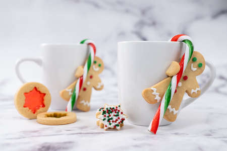 Christmas butter cookies ginger bread man hold candy cane hung to the side of a cup