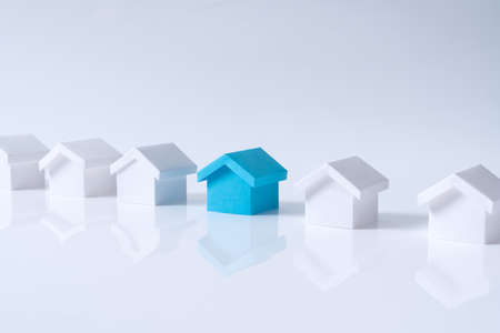 Blue house in among white houses for real estate property industry Stock Photo