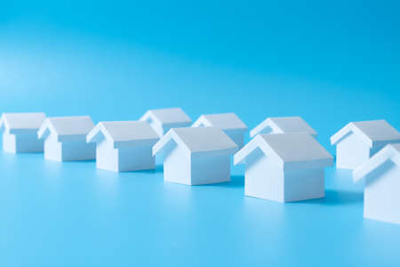 Row of miniature 3D white houses on blue background for real estate property, housing development or community