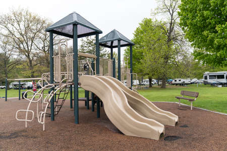 Children playground in public park surrounded by green trees