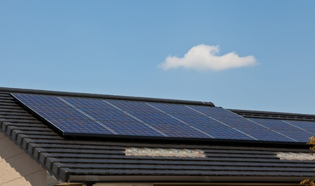This is a picture of solar panels that are installed on the roof of the house. Stock Photo