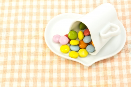 This is a picture of colorful chocolate and coffee cup placed on the table cloth  photo