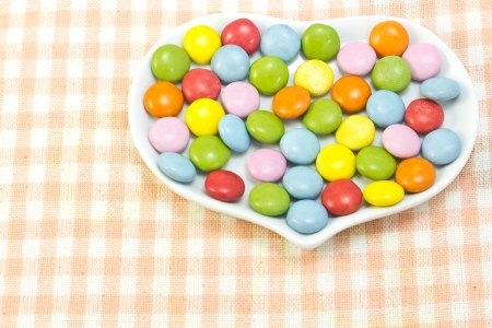 This is a picture of colorful chocolate placed on the table cloth  photo