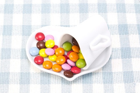 This is a picture of colorful chocolate and coffee cup placed on the table cloth. photo
