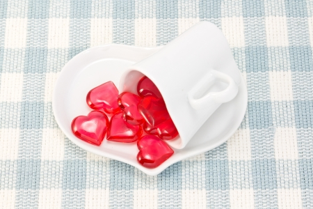 This is a picture of a red hearts and heart-shaped cup on the table photo