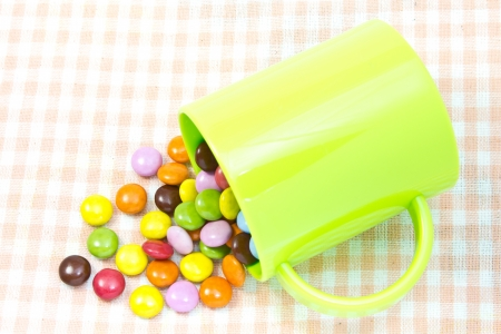This is a picture of colorful chocolate and mug placed on the table. Stock Photo