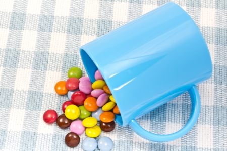 This is a picture of colorful chocolate and mug placed on the table. Stock Photo - 14539074