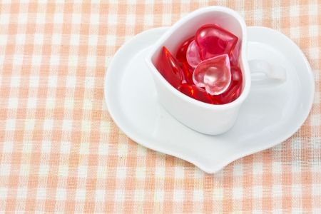 This is a picture of a red and pink hearts and heart shaped cup on the table. Stock Photo - 14539070