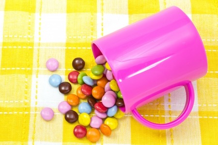 This is a picture of colorful chocolate and mug placed on the table. Stock Photo - 14539107