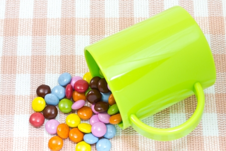 This is a picture of colorful chocolate and mug placed on the table. photo