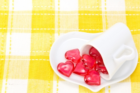 This is a picture of a red hearts and heart shaped cup on the table. photo
