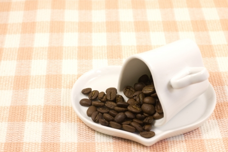 This is a picture of coffee beans and coffee cup on the table cloth  photo