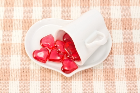 This is a picture of a red hearts and heart shaped cup on the table.