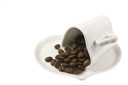 This is a picture of coffee beans and coffee cup on the table cloth. Stock Photo