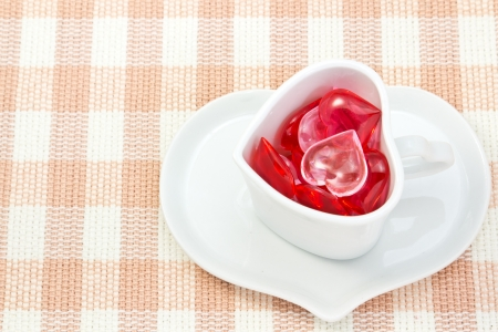 This is a picture of a red and pink hearts and heart shaped cup on the table  photo