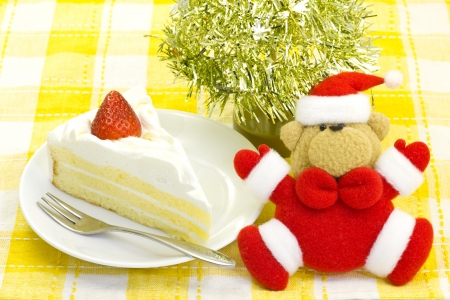 This is a photograph of a stuffed bear wearing a Santa Claus costume and shortcake. photo