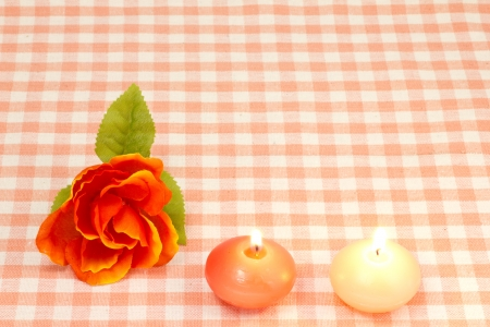 This is a picture of an artificial rose and candles. photo
