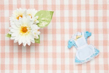 これはミニチュアのメイド服と花の写真です。