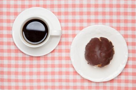 creampuff: a chocolate cream puff and coffee.
