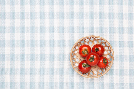 These are the tomatoes on the table and put it in a basket.  Stock Photo