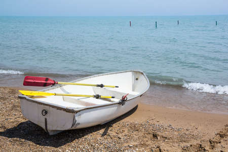 White rowboat with yellow and red oars resting on the pebbly shore while being lapped by the surf as it looks out onto the distant horizon of Lake Michigan in the sunshine Stock Photo