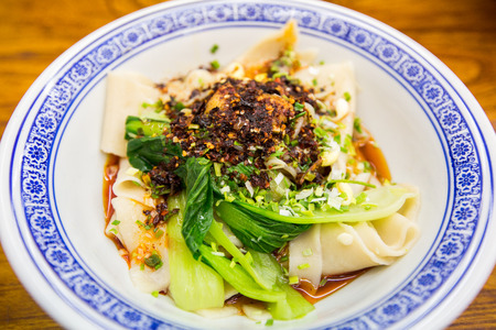 Bowl of flat broad Chinese noodles dish in Xian