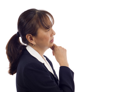 Asian American senior businesswoman showing pensive expression with hand on chin isolated over white background
