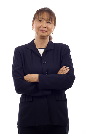 Portrait of a confident senior Asian business woman with arms folded isolated over white background Stock Photo