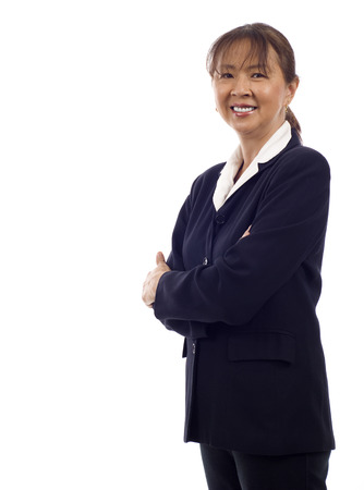 Asian American senior businesswoman standing with hands folded against white background Stock Photo