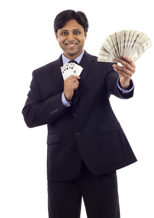 Friendly Indian business man holding playing cards and money isolated over white background photo