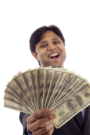 Laughing Indian business man holding a handful of money isolated over white photo