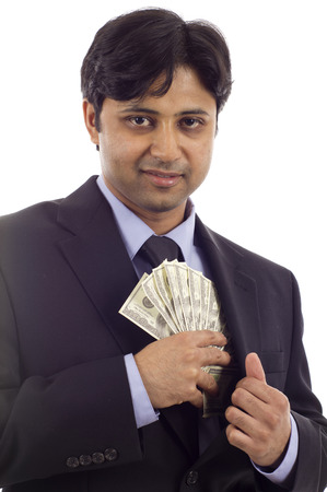 putting money in pocket: An Indian business man putting money in his pocket isolated over white background Stock Photo