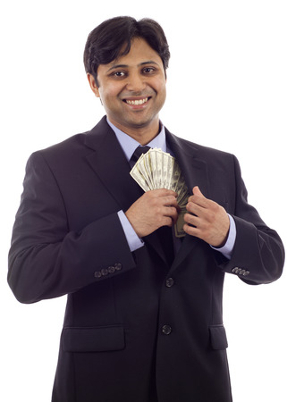 venality: An Indian business man in a black suit putting money in his pocket isolated over white background